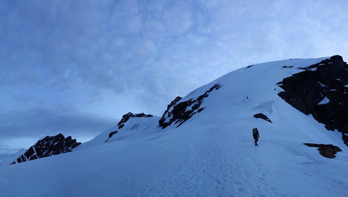 Prime luci salendo alla Roccia Nera: a destra il pendio nevoso della salita alla cresta con la Roccia Nera (dx). Oltre la gobba nevosa il primo dente roccioso è il Gemello del Breithorn, poi l'Orientale, la dentellata cresta rocciosa a tre salti del Centrale e in piccolo a sinistra l'Occidentale